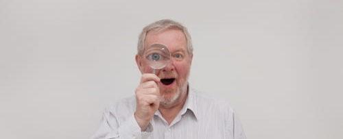 おじさんが虫眼鏡でこちらを覗いてる画像