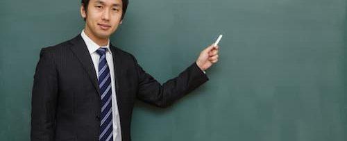 黒板の前で男の人が指をさしてる画像||競艇予想サイト 口コミ 評価 評判 検証 当たる 当たらない