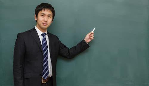 黒板の前で男の人が指をさしてる画像