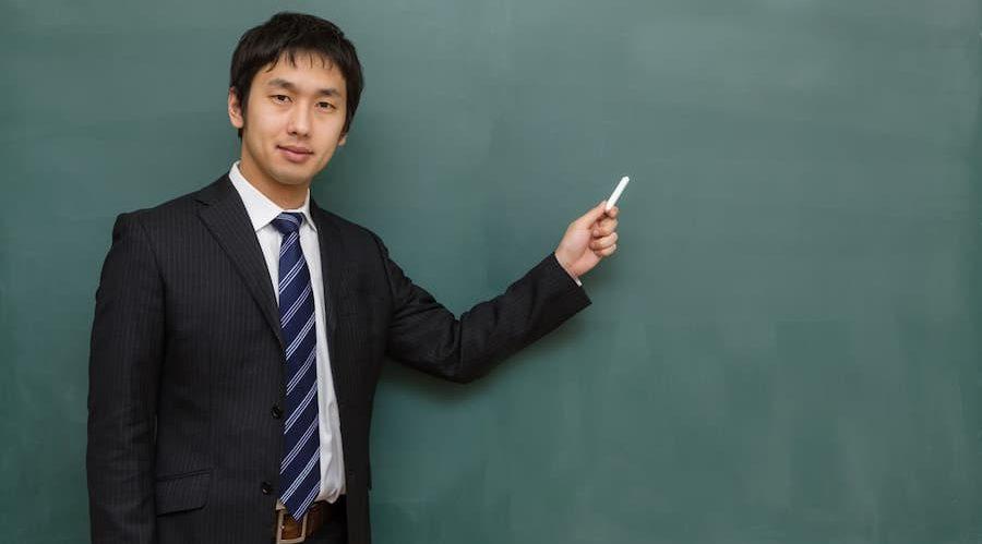 黒板の前で男の人が指をさしてる画像  競艇予想サイト 口コミ 評価 評判 検証 当たる 当たらない