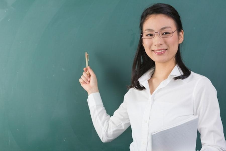 女性の教師が黒板を差しながら何かを教えてる画像||競艇予想サイト 口コミ 評価 評判 検証 当たる 当たらない