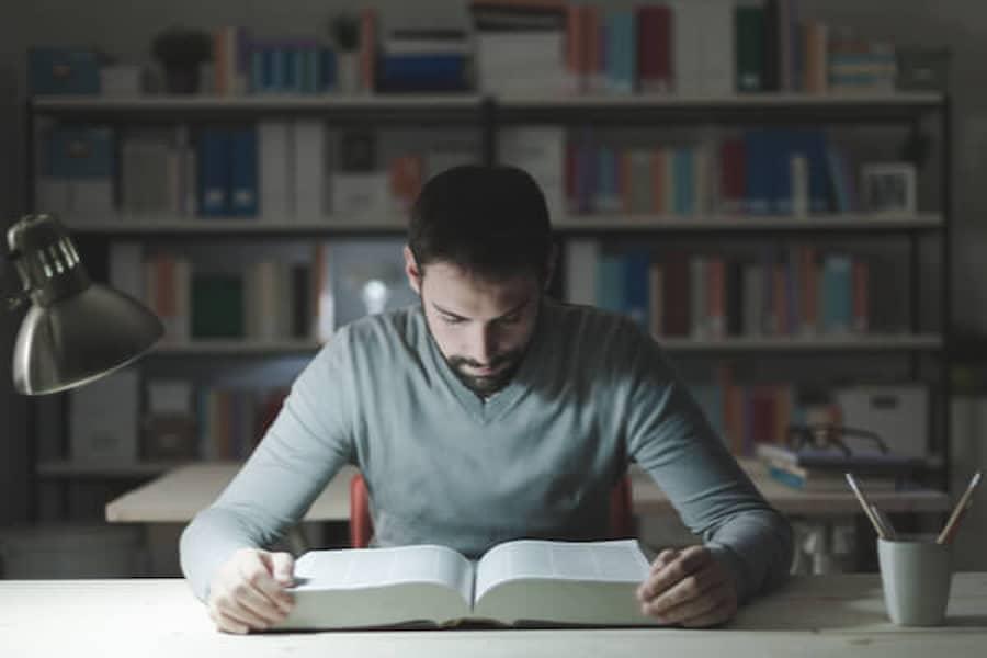 図書館で本を読む男性||競艇予想サイト 口コミ 評価 評判 検証 当たる 当たらない