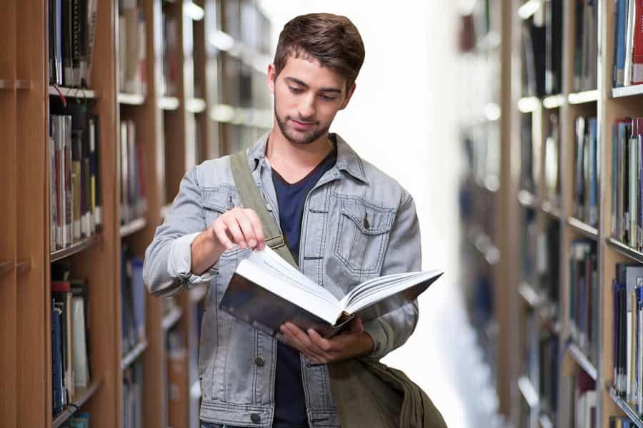 図書館で本の立ち読みをしている男性の画像||競艇予想サイト 口コミ 評価 評判 検証 当たる 当たらない